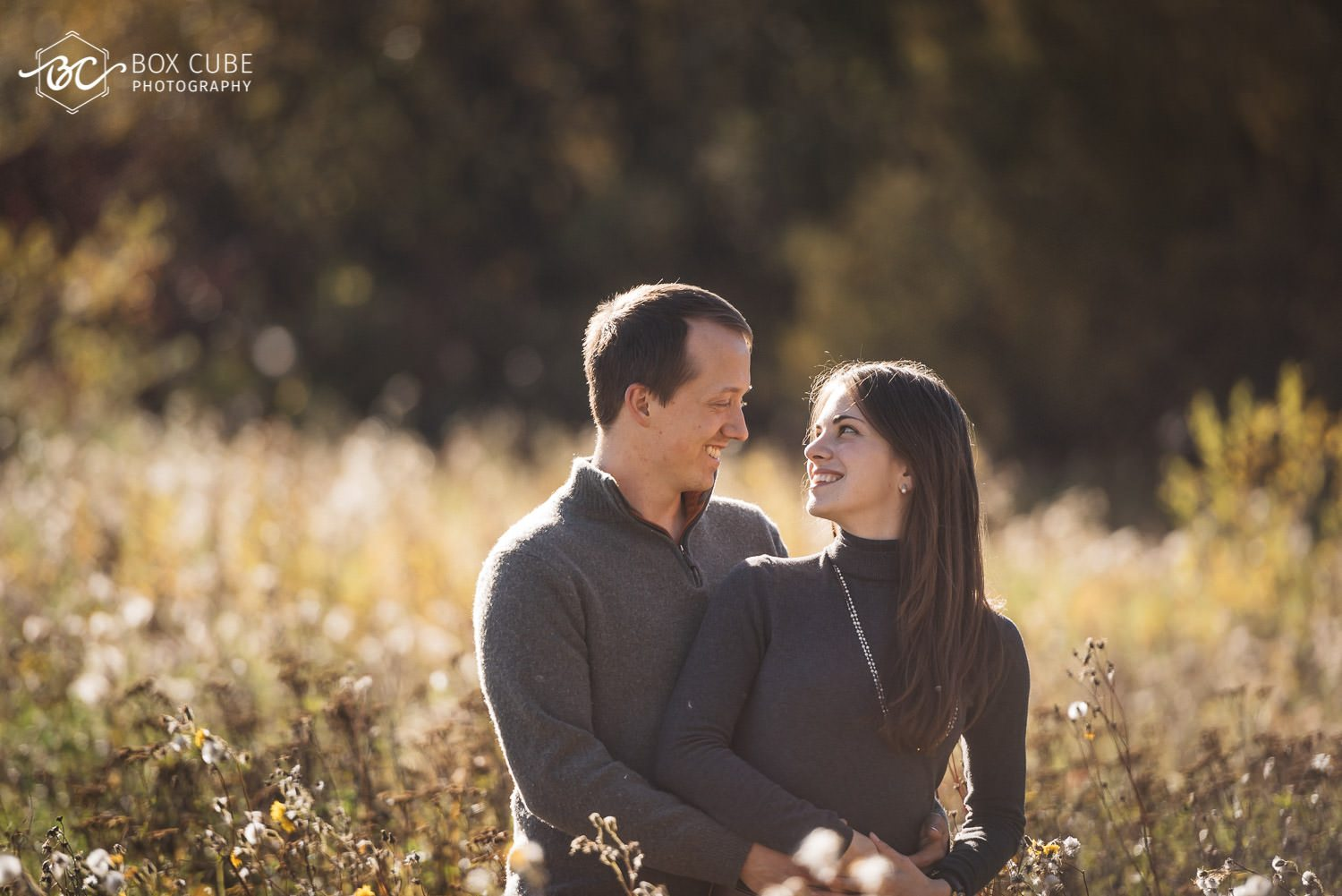 engagement photos at peace hills park, wetaskiwin, alberta. Couple standing in trees.