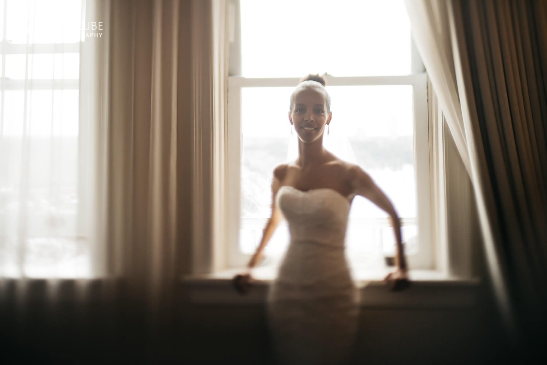 bride standing against the window for her portrait at the Hotel Fairmont Macdonald, Edmonton