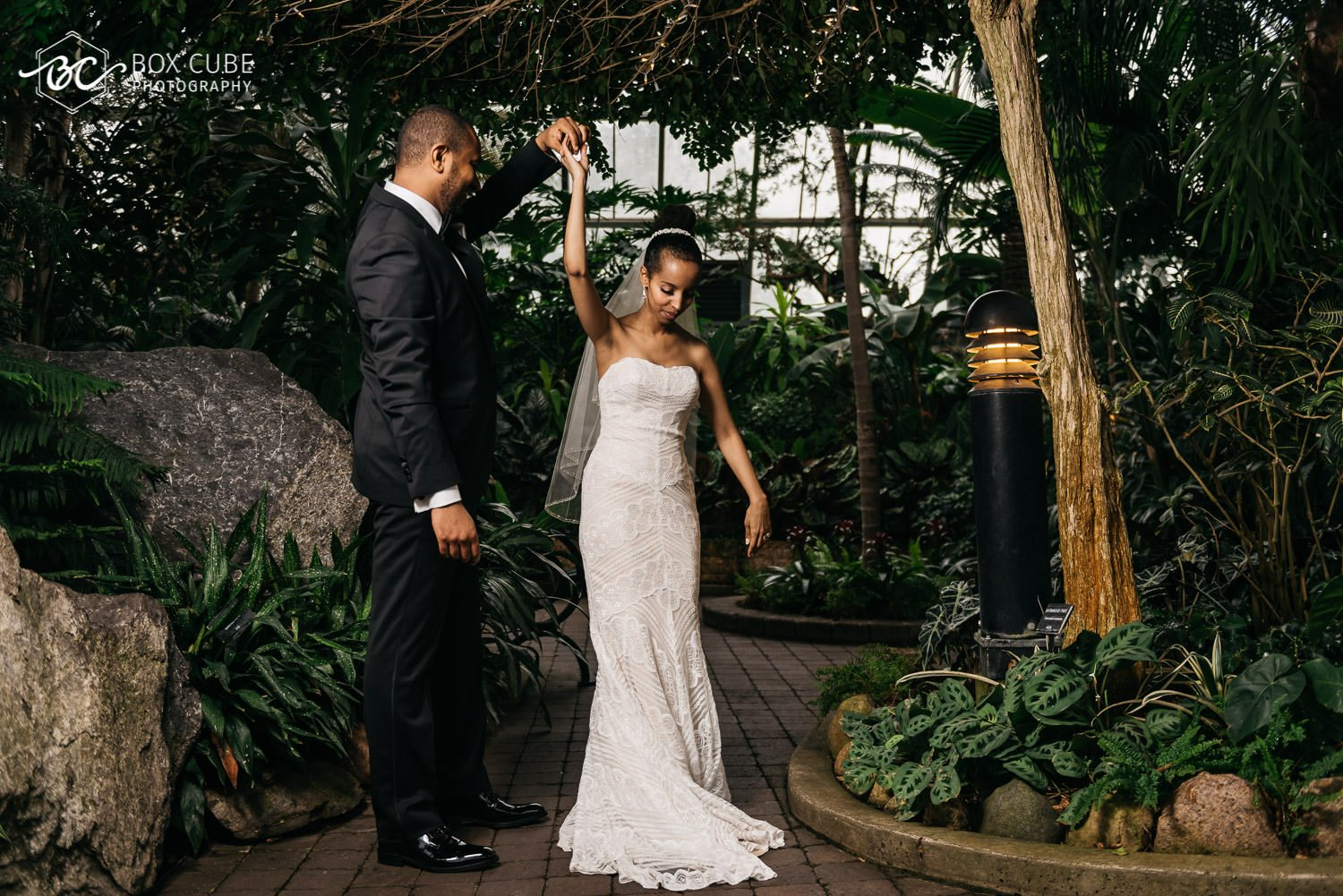 creative formal wedding portraits at muttart conservatory where bride is hugging the groom