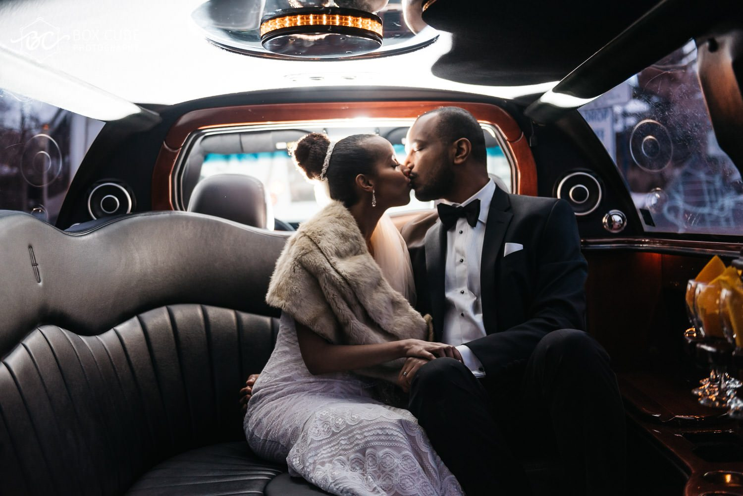 bride and groom in limousine kissing
