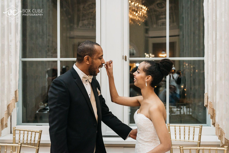 bride feeding groom cake at wedding at hotel fairmont macdonald
