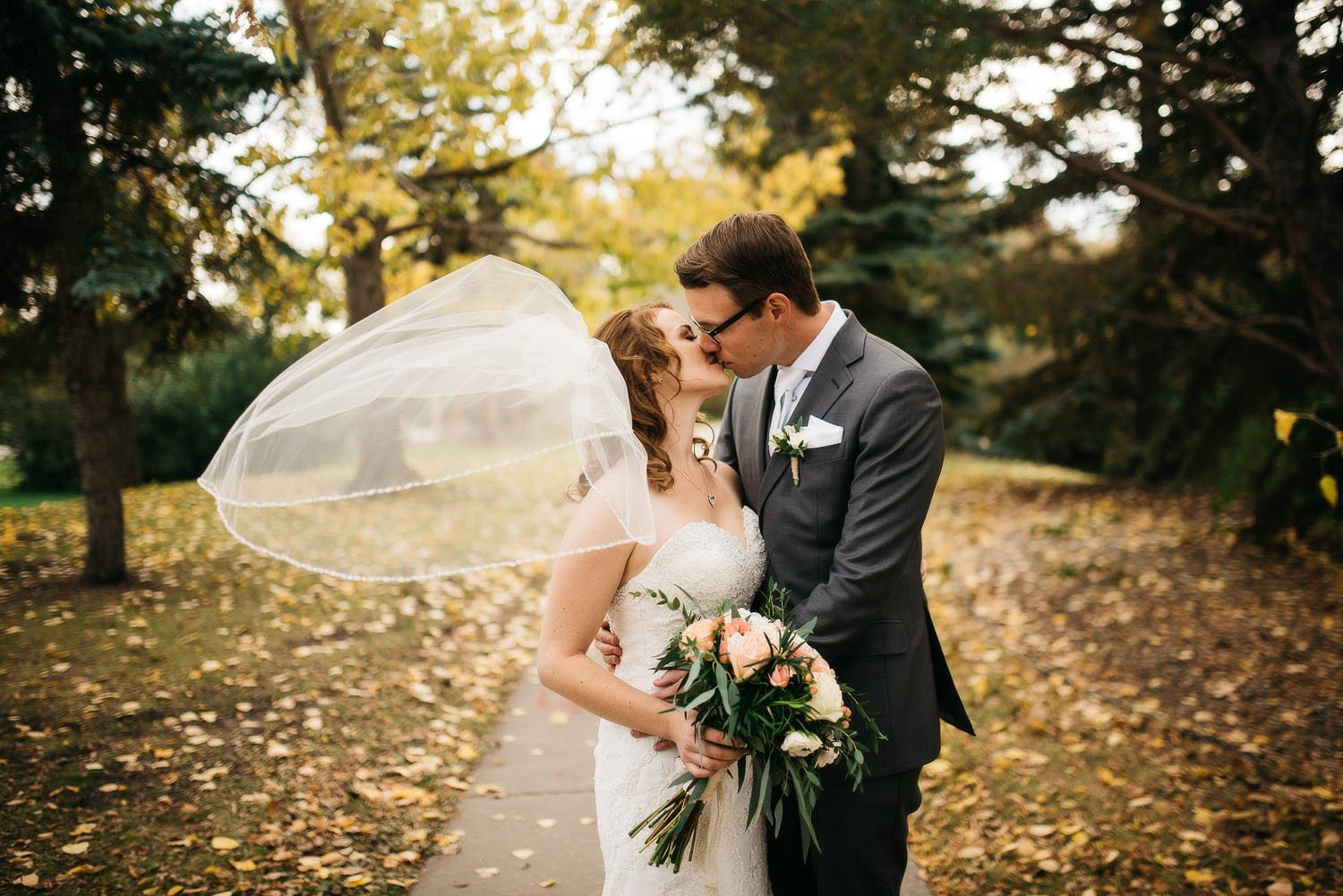 red willow park wedding couple kissing and bride's veil flying with fall colors in the background photo