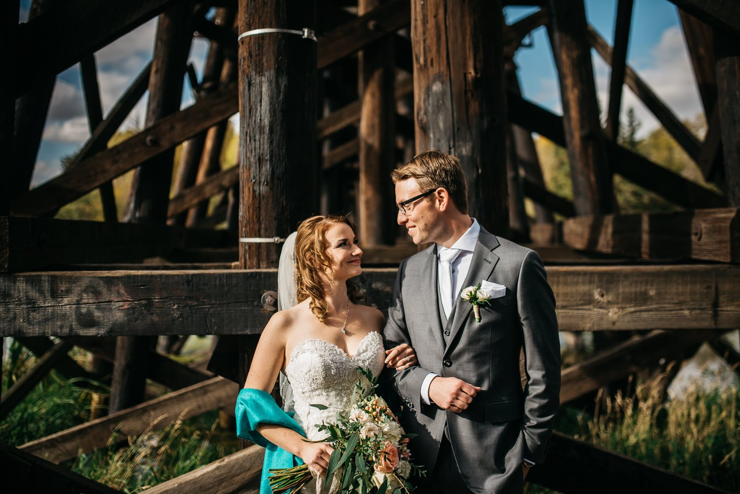red willow park wedding edmonton couple looking at each other under train trestle photo