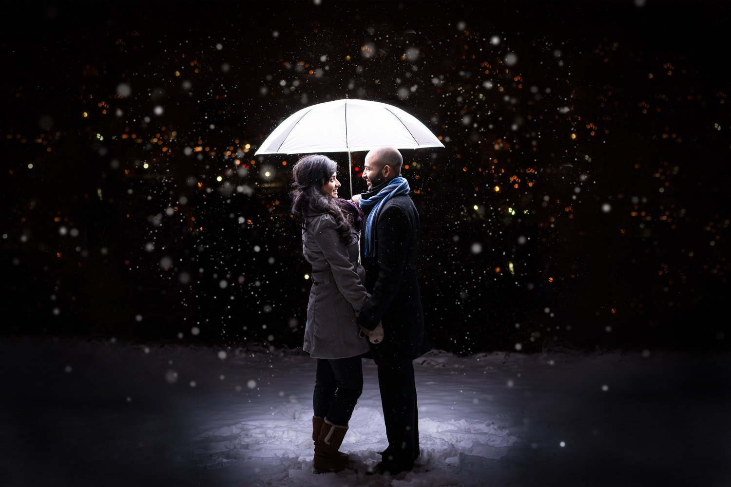 engagement session at saskatchewan drive couple standing under umbrella with snow falling in the background magical photo