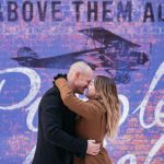 "couple hugging in front of purple wall with a plane in the background and a quote saying ""above them all"""