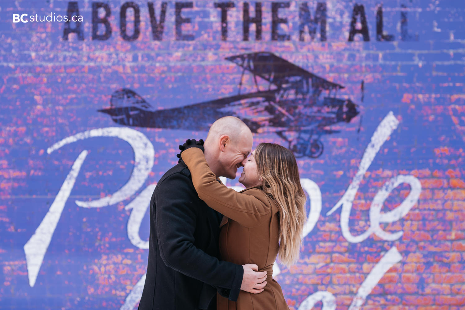 """couple hugging in front of purple wall with a plane in the background and a quote saying """"above them all"""""""
